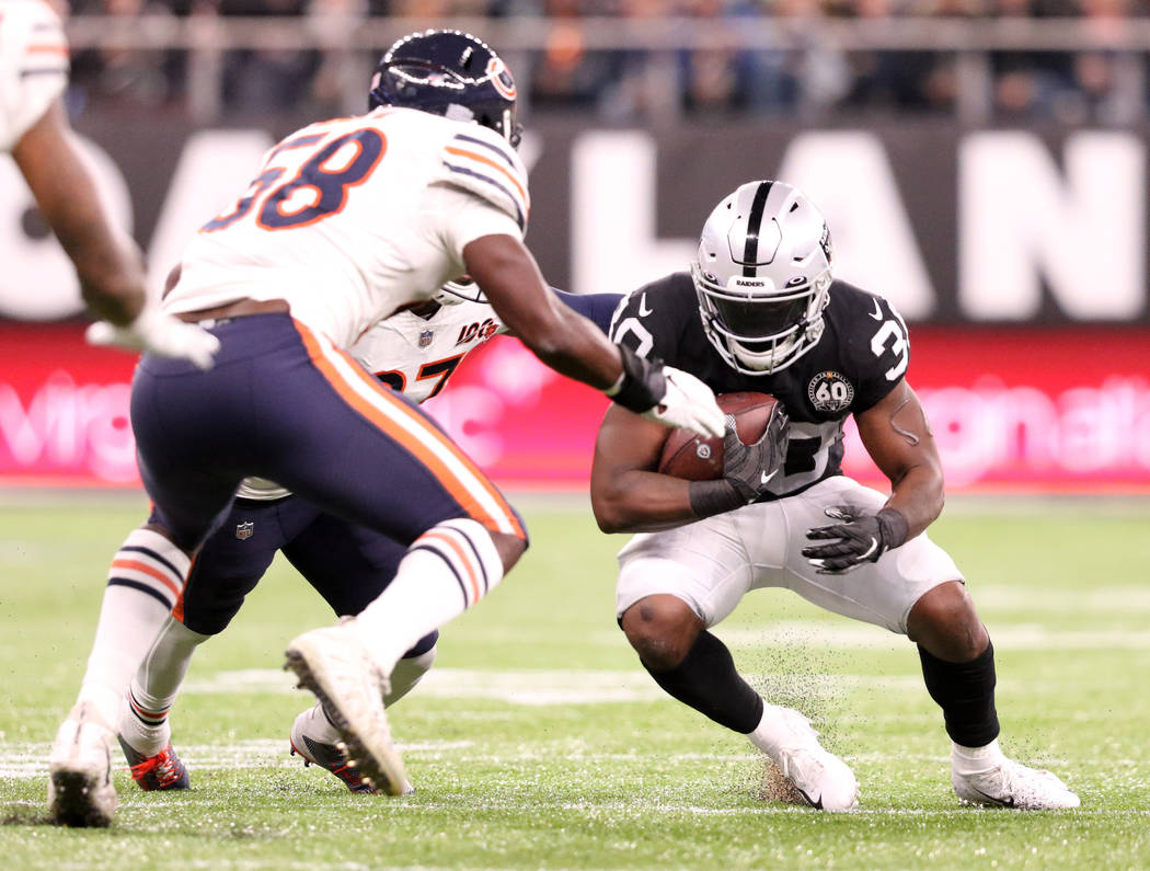 Oakland Raiders running back Jalen Richard (30) looks for room to run as Chicago Bears inside l ...