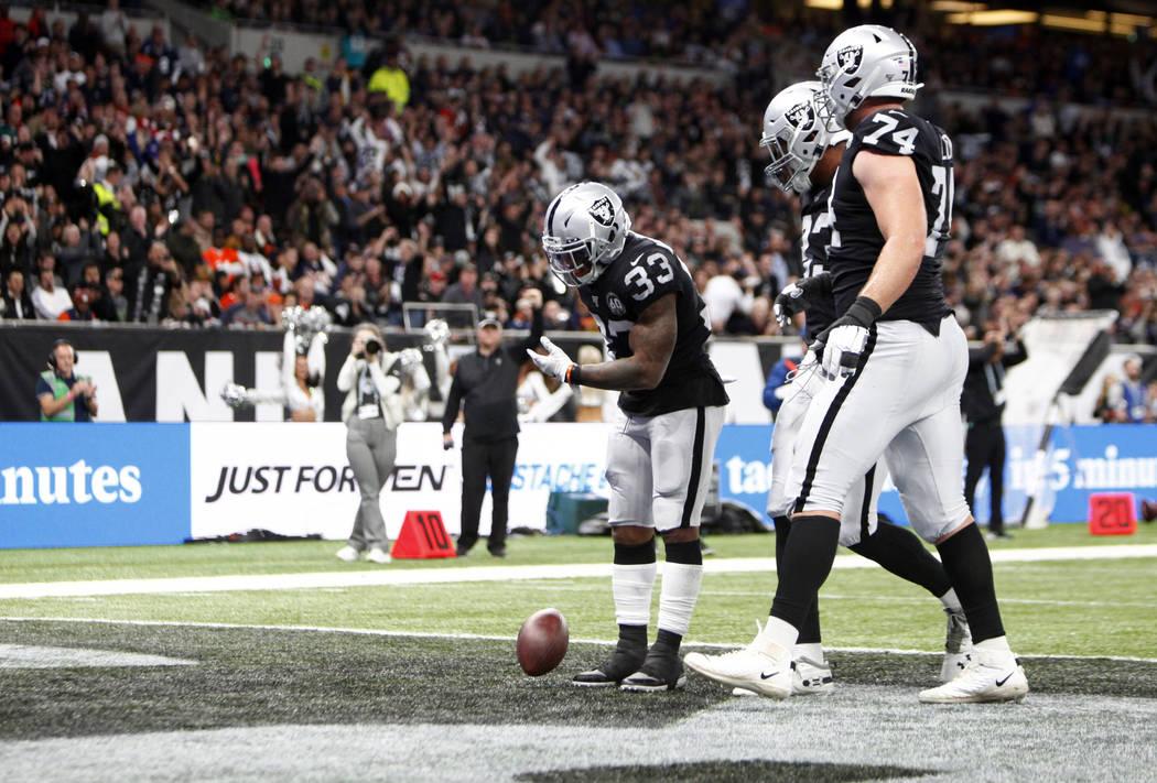 Oakland Raiders running back DeAndre Washington (33) bows after scoring a touchdown as tight en ...
