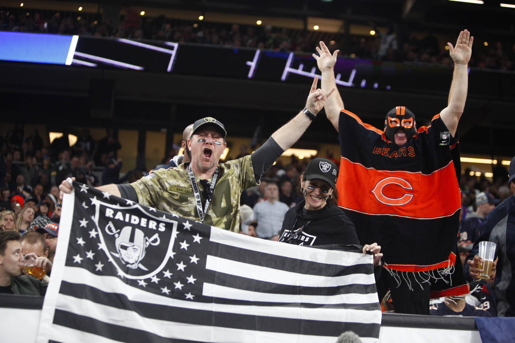 Oakland Raiders fans hold up a flag as a Chicago Bears fan cheers during an NFL game between th ...