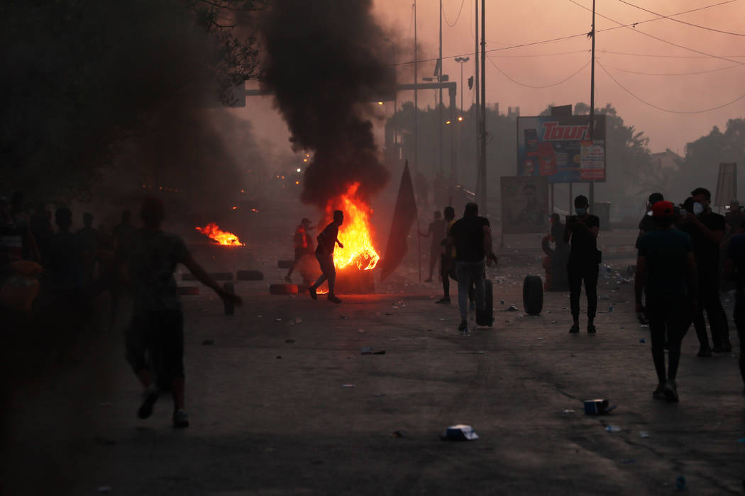 Anti-government protesters set fires and close a street during a demonstration in Baghdad, Iraq ...