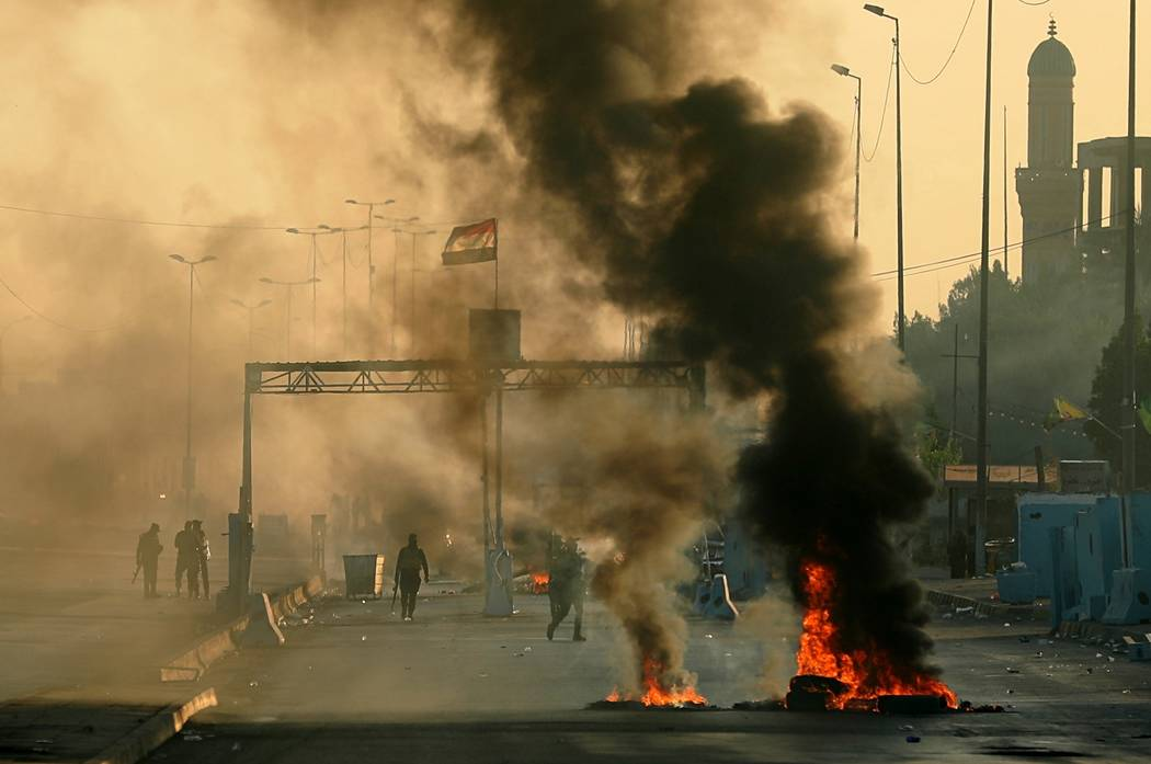 Iraqi security forces fire tear gas to disperse anti-government protesters who set fires and cl ...