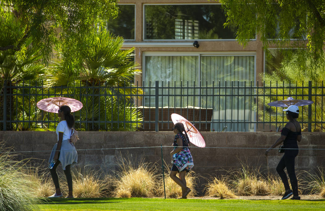 Attendees stay cool under umbrellas as they walk along hole 9 during the final round of Shriner ...