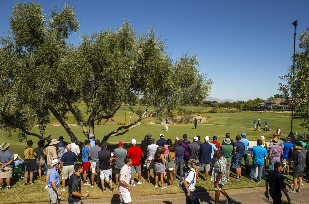 The gallery crowds around as Kevin Na and Patrick Cantlay approach the green at hole 3 during t ...
