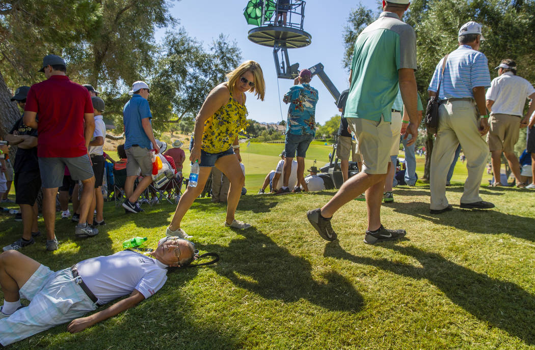 A fan is passed out near the green at hole 8 during the final round of Shriners Hospitals for C ...