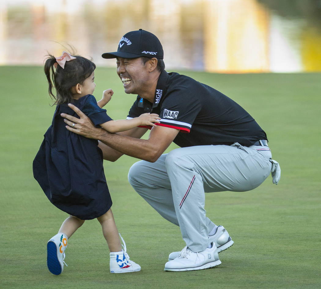 Kevin Na catches his daughter Sophie, 3, who runs to him as he celebrates his victory on the s ...