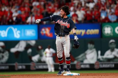 Atlanta Braves' Dansby Swanson celebrates after hitting an RBI-double during the ninth inning i ...