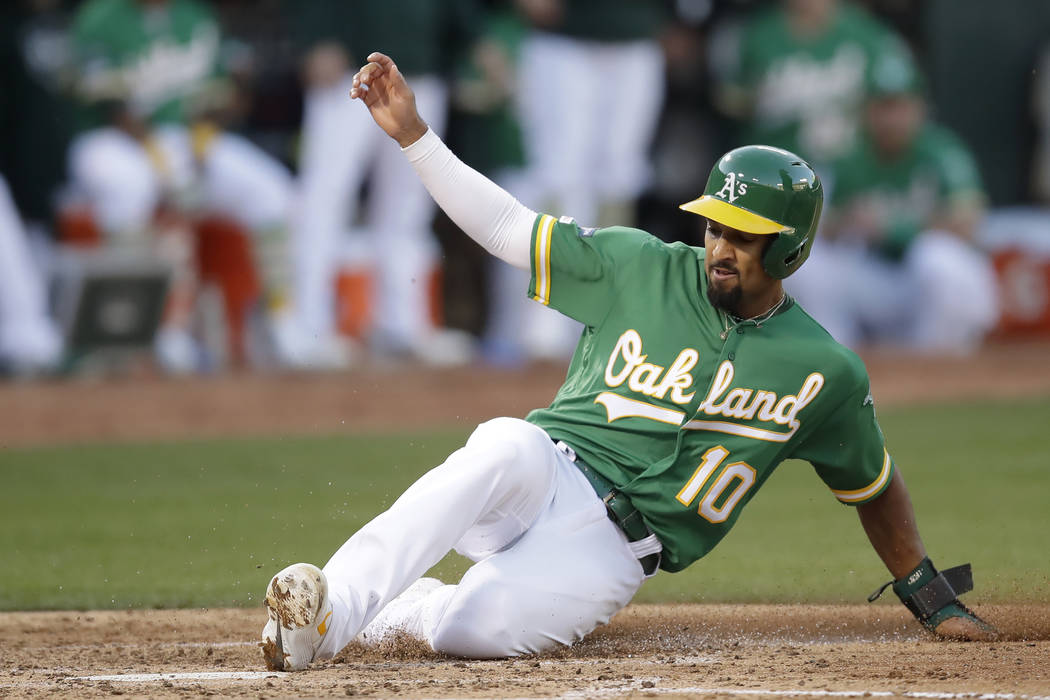 Oakland Athletics' Marcus Semien (10) scores against the Tampa Bay Rays during the third inning ...