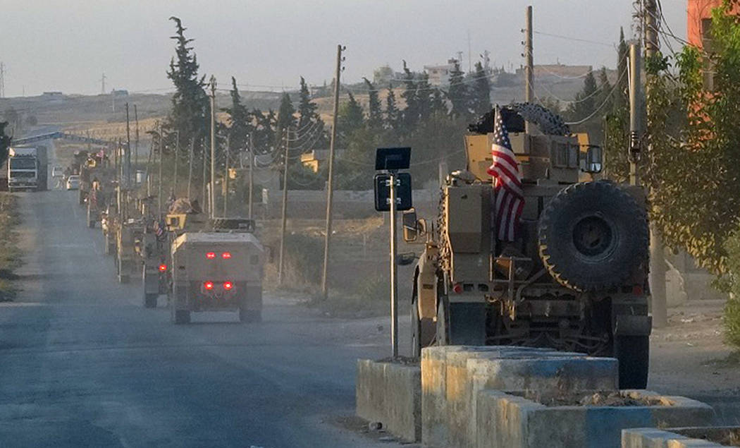 In this image provided by Hawar News Agency, ANHA, U.S. military vehicles travel down a main ro ...
