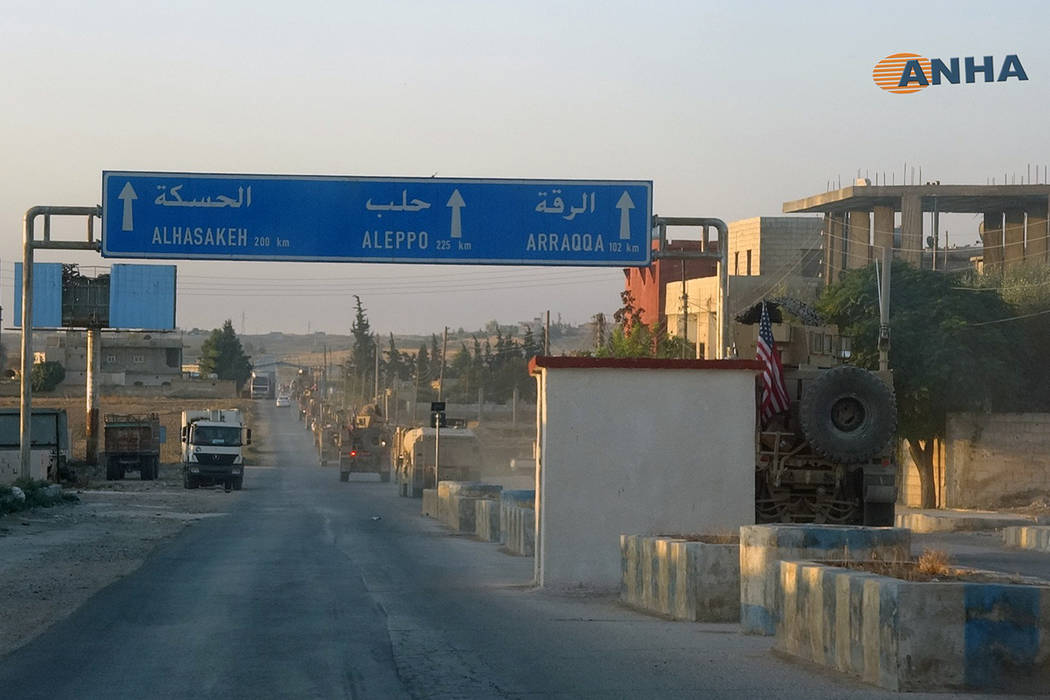 In this image provided by Hawar News Agency, ANHA, a line of U.S. military vehicles travel dow ...