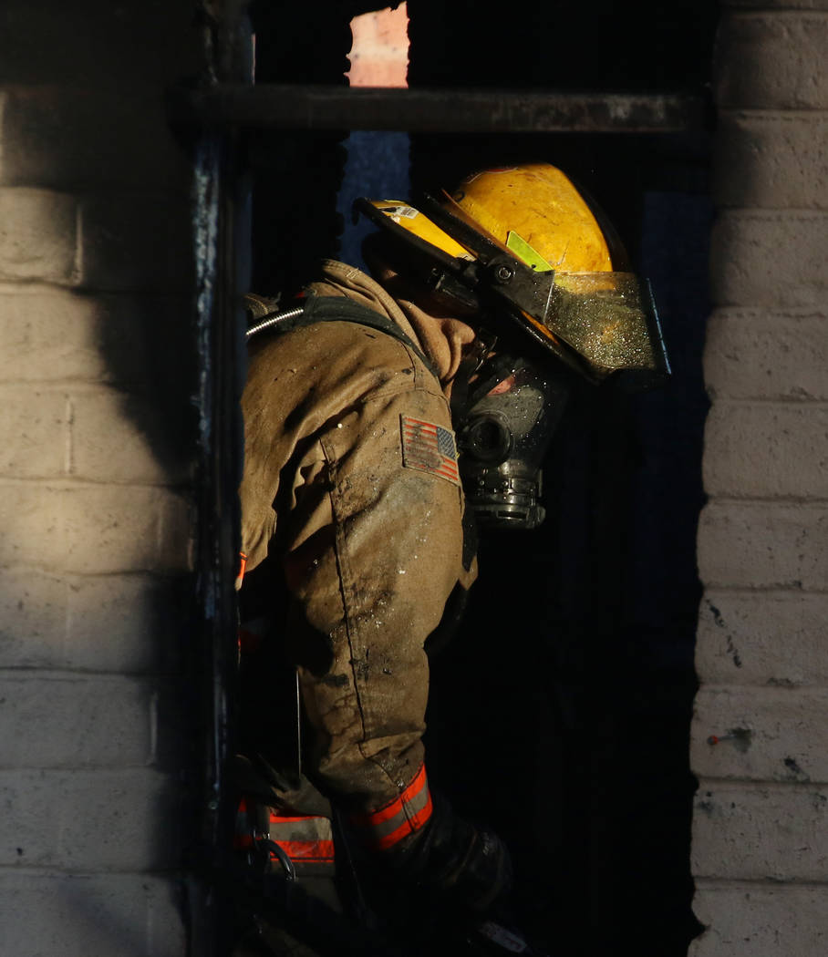 A Clark County firefighter battles a fire in a commercial area at 824 E. Sahara Ave. on Monday, ...