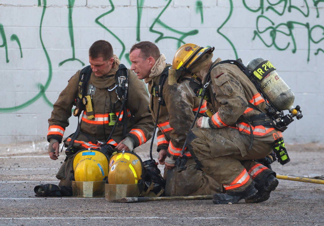 The Clark County firefighters take a break after battling a fire in a commercial area at 824 E. ...
