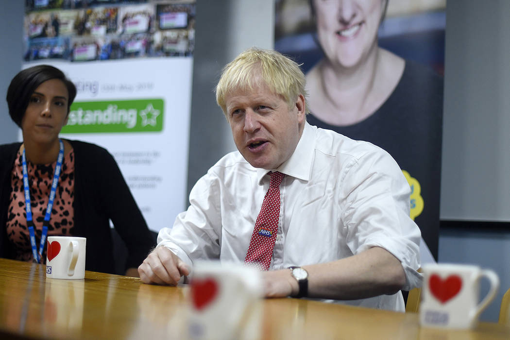 Britain's Prime Minister Boris Johnson speaks to health professionals as he visits Watford Gene ...