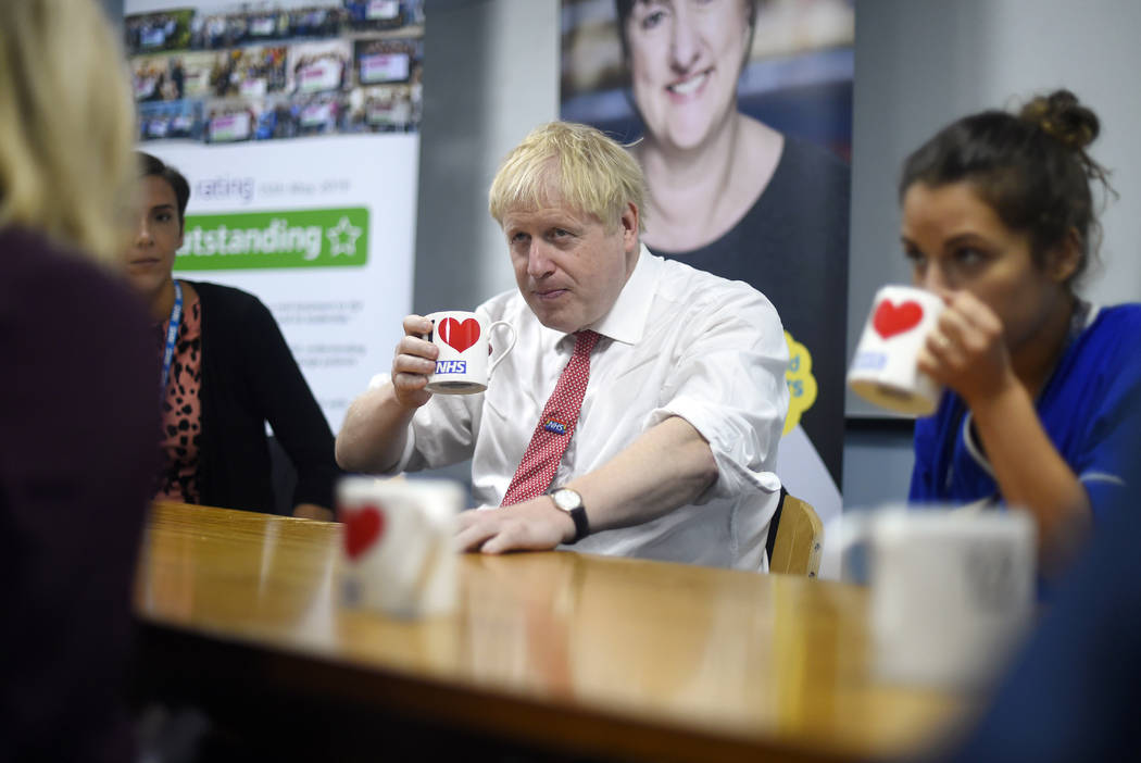 Britain's Prime Minister Boris Johnson speaks to mental health professionals as he visits Watfo ...