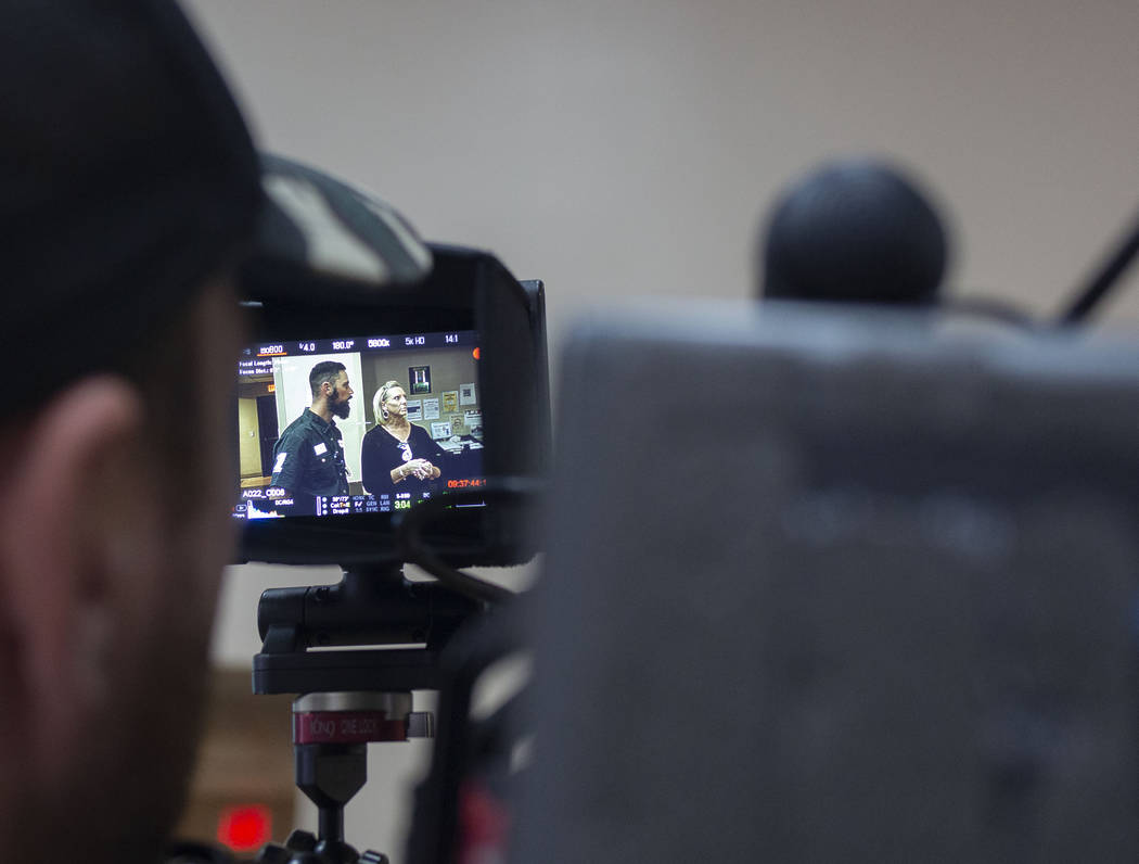 A camera team records pastor Brandan Thomas from Winchester Rescue Mission in Virginia, left, a ...