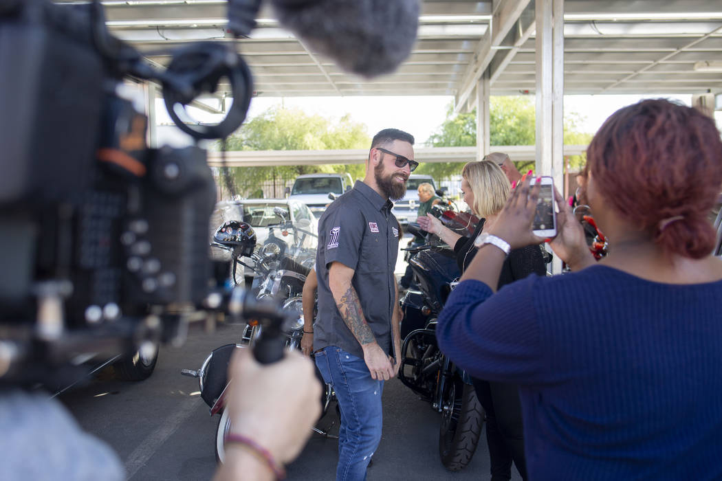 A camera team documents pastor Brandan Thomas from Winchester Rescue Mission in Virginia, left, ...