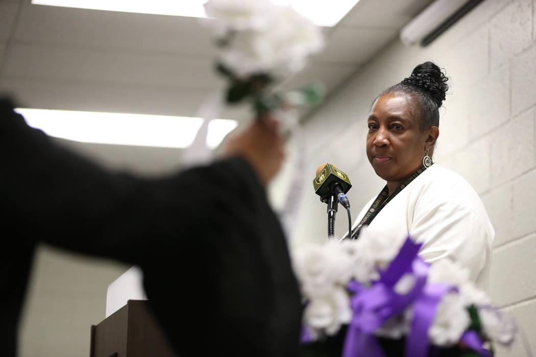Las Vegas Metropolitan Police Department victims advocate Regina Porter watches as a flower wit ...