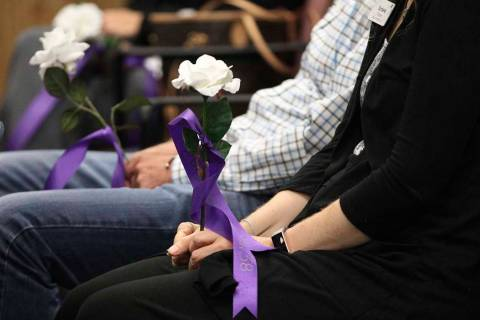 People hold flowers with the names of domestic violence victims killed in the last year during ...