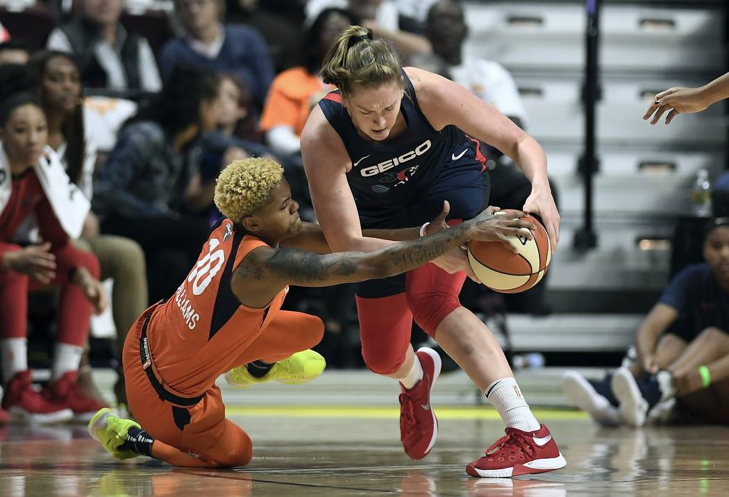 Connecticut Sun's Courtney Williams, left, trites to take the ball from Washington Mystics' Emm ...