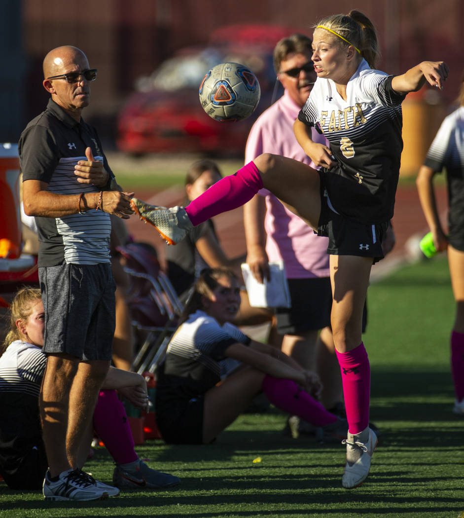 Faith Lutheran's Mackenzie Folk (8) attempts to save the ball with a kick on the sidelines vers ...