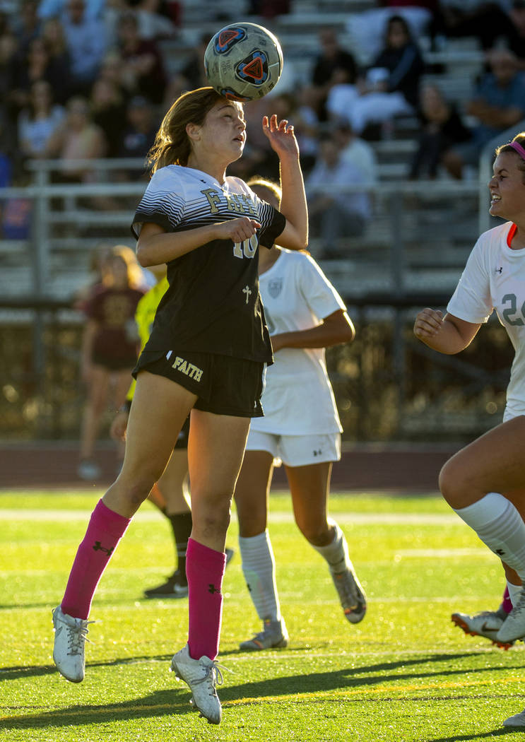 Faith Lutheran's Ari Gronauer (10, left) heads the ball away from Arbor View defenders during t ...