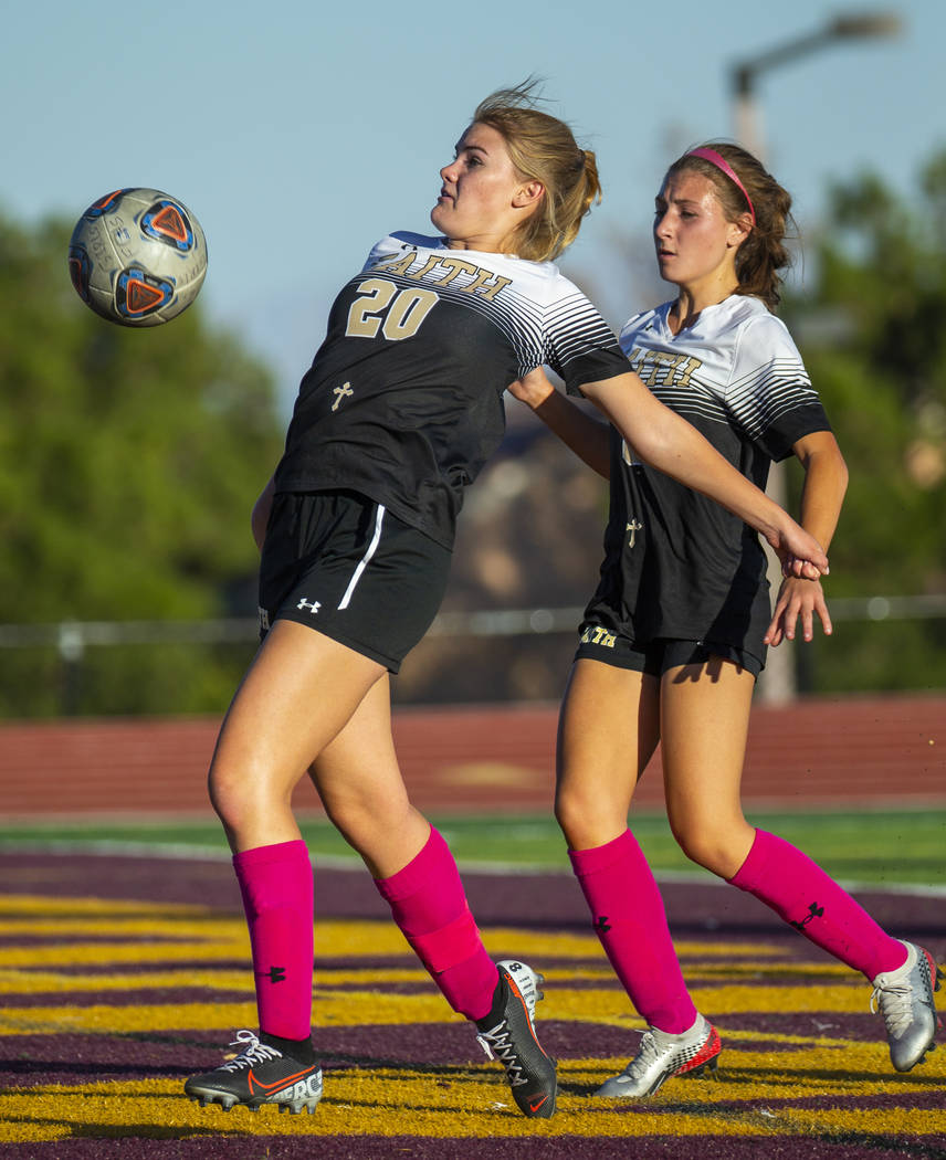 Faith Lutheran's Amelia McManus (20, left) bounces the ball off her midsection and into the Arb ...