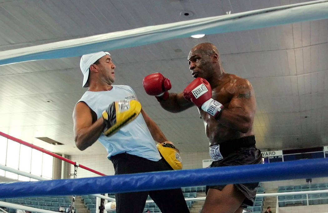 FILE - In this June 7, 2005, file photo, former Heavyweight Champion Mike Tyson, right, spars w ...