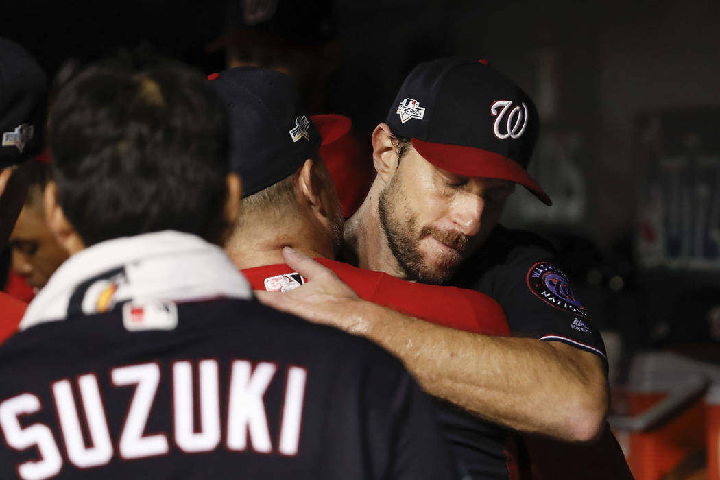 Washington Nationals starting pitcher Max Scherzer (31) is greeted by teammates in the dugout i ...