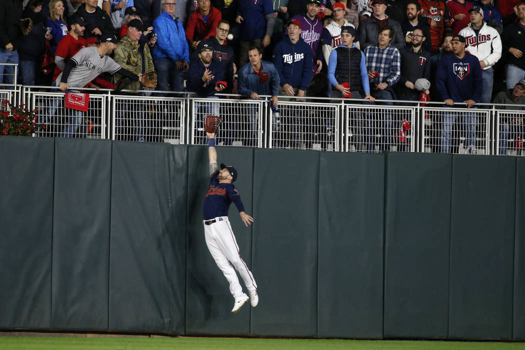 Minnesota Twins left fielder Jake Cave makes a leaping attempt at a home run hit by New York Ya ...