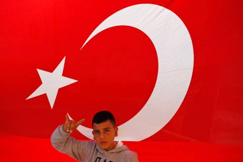 A youth flashes a hand gesture representing the Turkish far-right gray wolves organisation as h ...