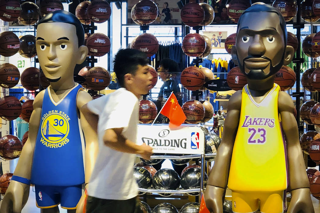 A man walks past statues of NBA players Stephen Curry of the Golden State Warriors, left, and L ...
