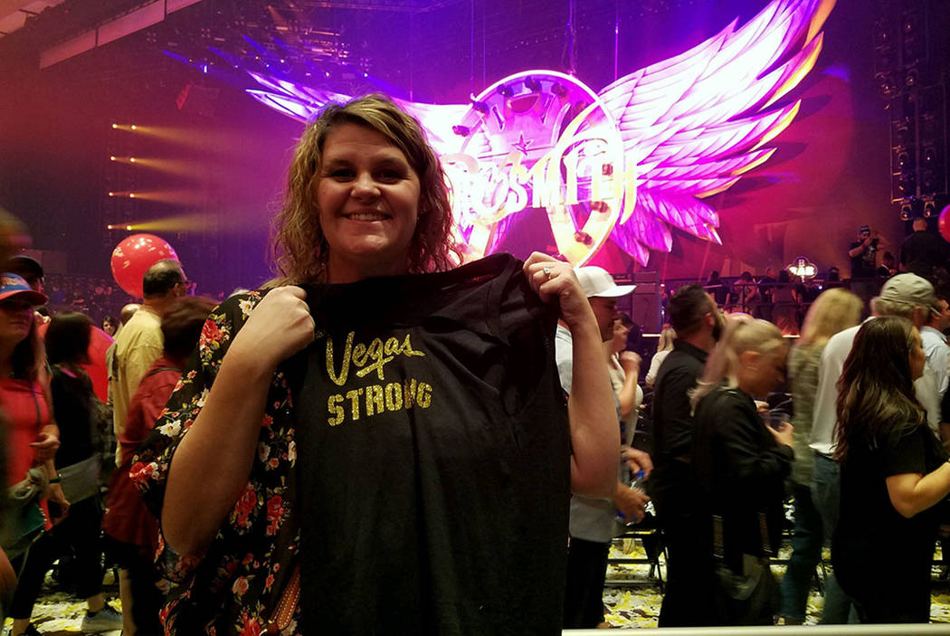 Barbie Dahl of Las Vegas shows off the Vegas Strong T-shirt tossed to the crowd after Aerosmith ...