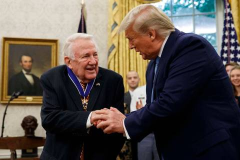 President Donald Trump shakes hands with former Attorney General Edwin Meese after presenting h ...