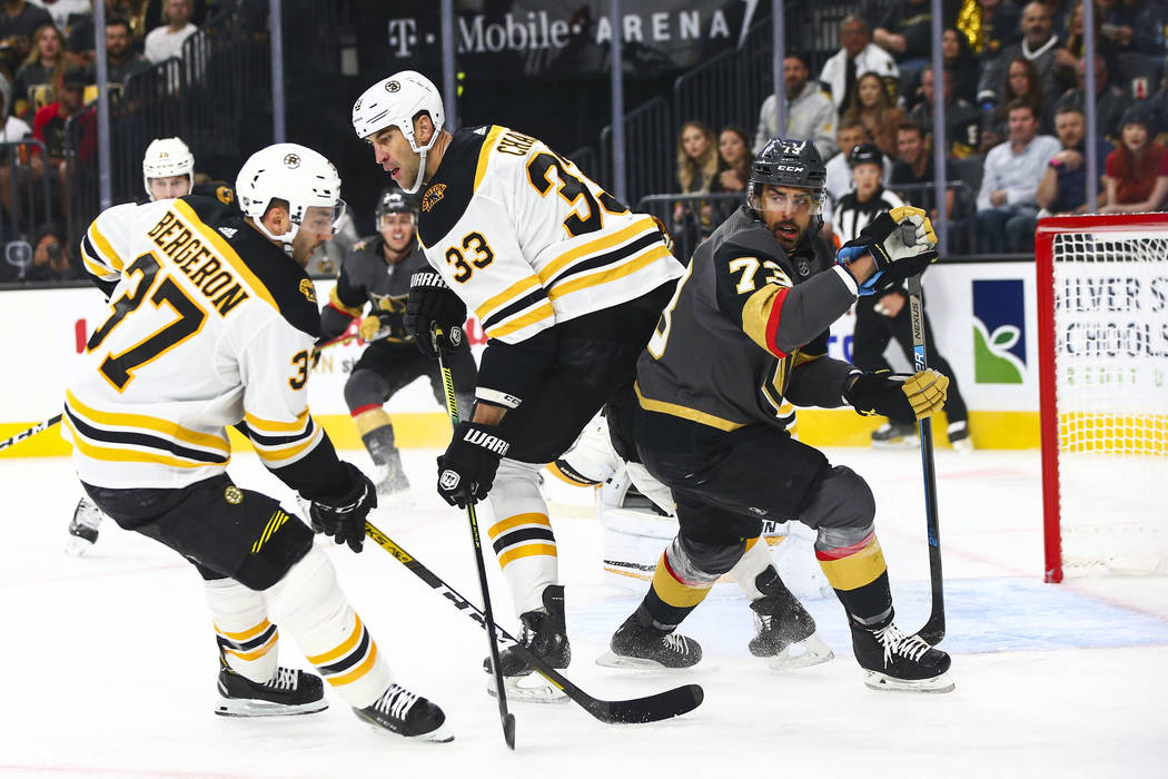 Boston Bruins' Zdeno Chara (33) and Golden Knights' Brandon Pirri (73) look for the puck during ...