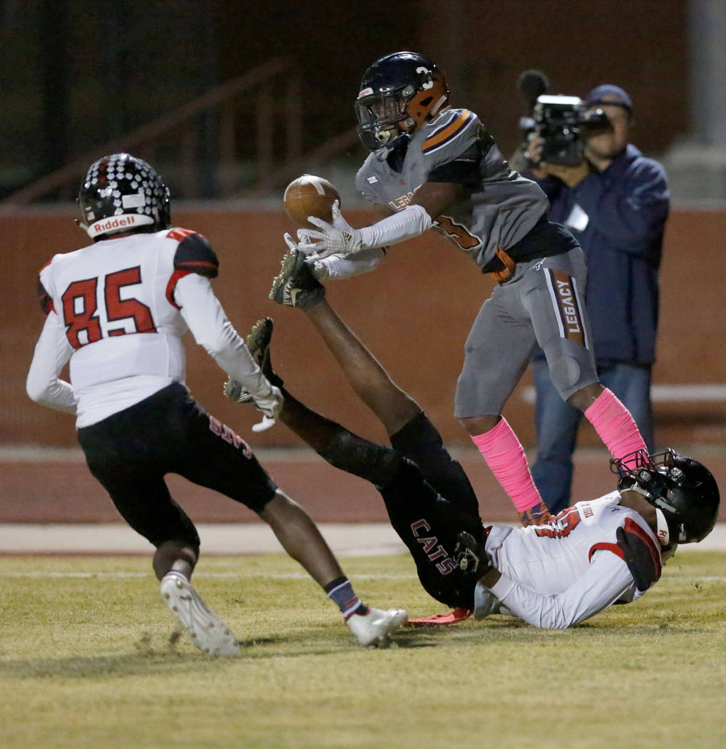 Legacy's Anthony Myles, left, catches a pass as Las Vegas' Flomar Hunt, bottom, falls down dur ...
