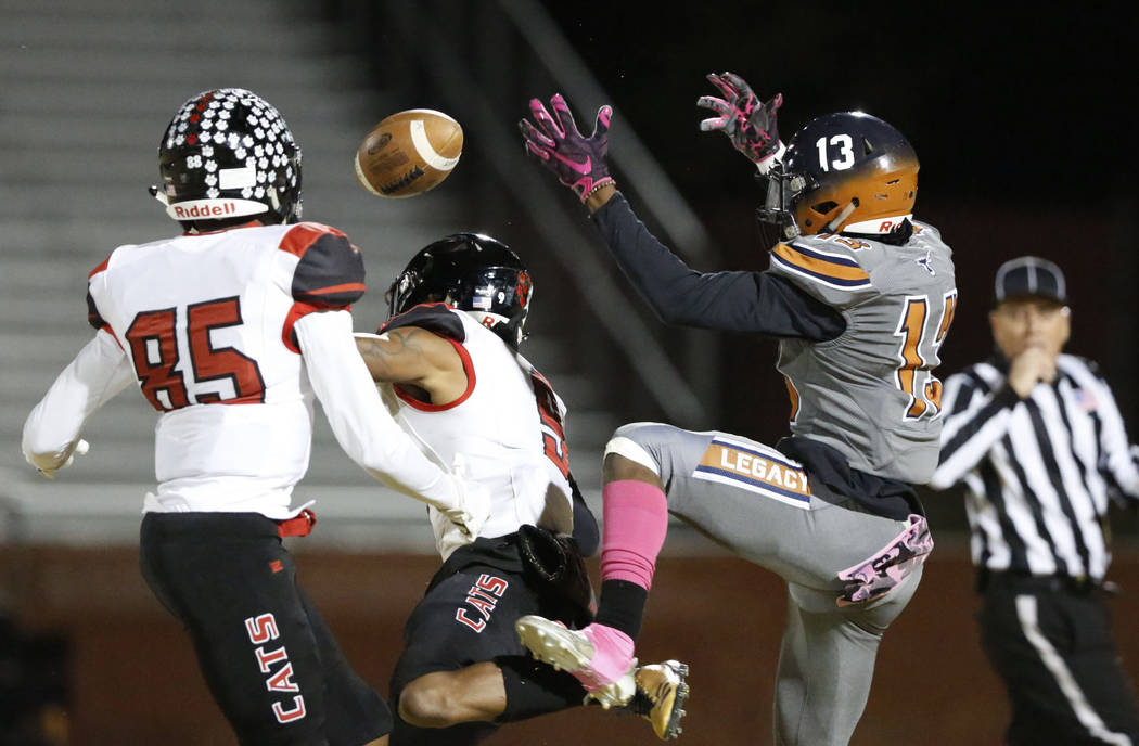 Legacy's Aaron Holloway (13) cannot catch a pass as Las Vegas' Christian Flores (85) and Devyn ...