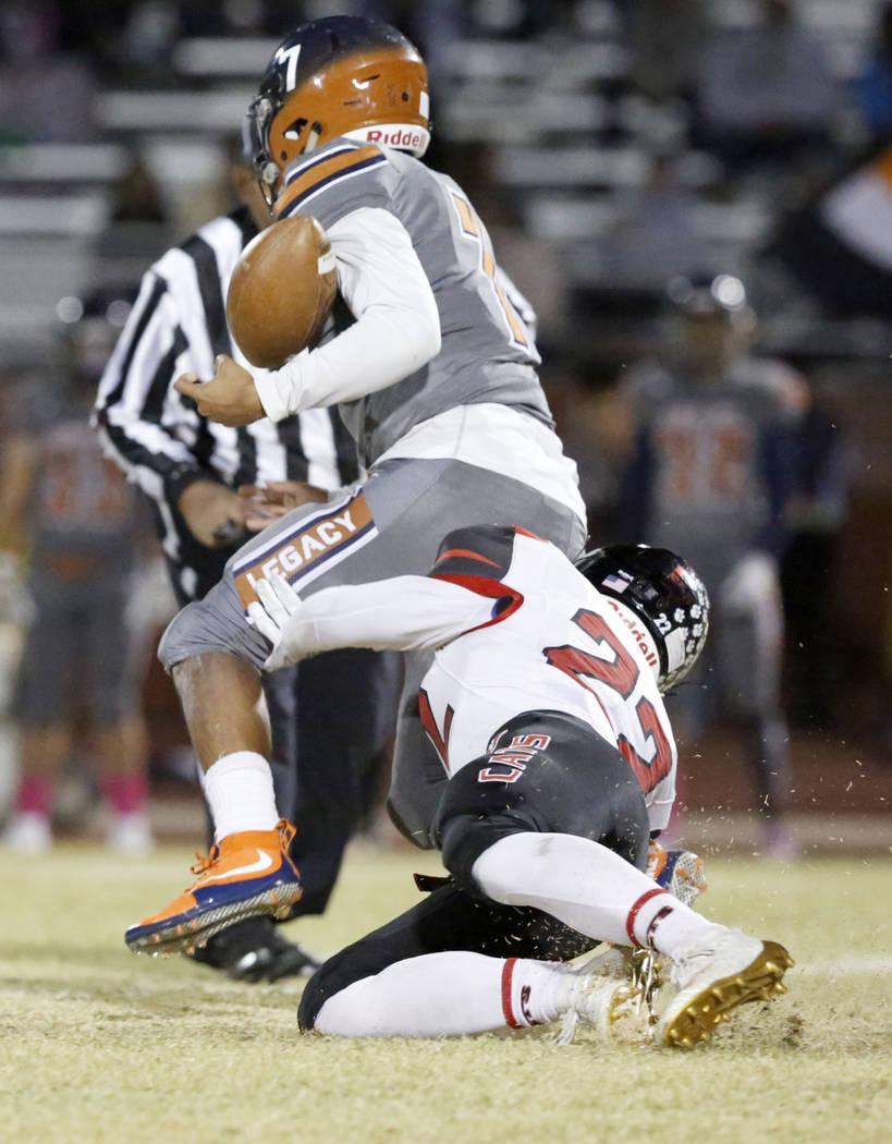 Legacy's quarterback Evan Olaes (7) loses a ball as Las Vegas' James Dunn tackles during the fi ...