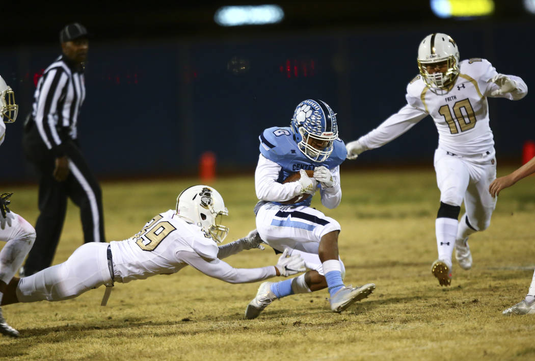 Centennial's Gerick Robinson (6) gets stopped by Faith Lutheran's Jaden Rhodes (39) and Faith L ...