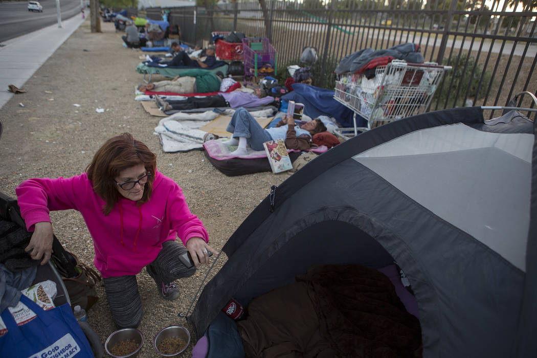 Jody Mathews, who is homeless, feeds her two dogs next to her tent where she stays along Las Ve ...