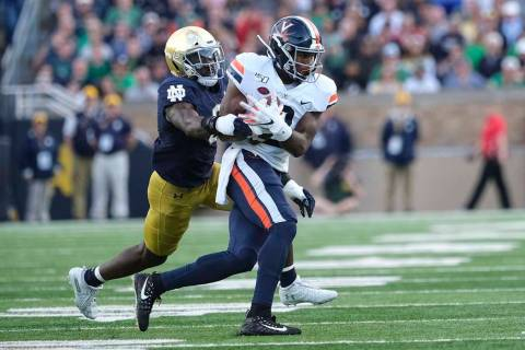 Virginia wide receiver Joe Reed (2) runs after making a catch in front of Notre Dame linebacker ...