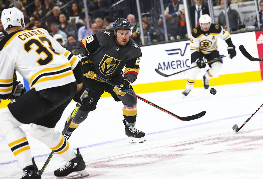 Golden Knights' William Carrier (28) sends the puck past Boston Bruins' Zdeno Chara (33) during ...