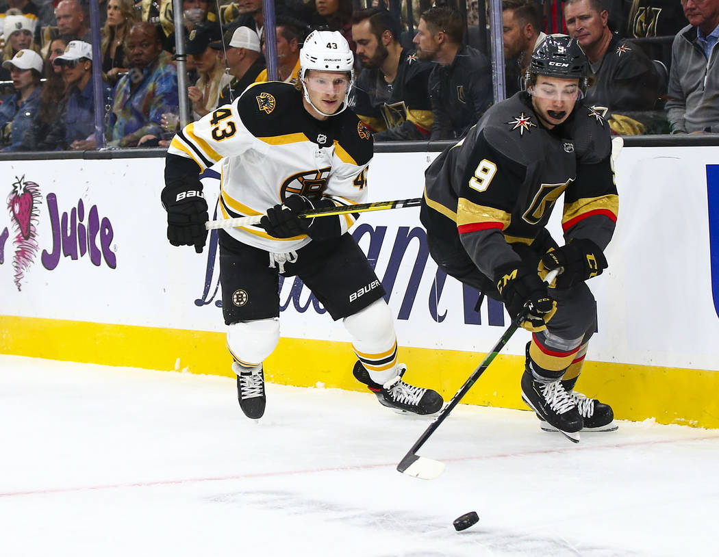 Golden Knights' Cody Glass (9) moves the puck in front of Boston Bruins' Danton Heinen (43) dur ...