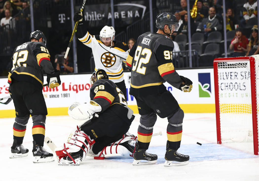 The Boston Bruins get the puck past Golden Knights goaltender Marc-Andre Fleury (29) during the ...