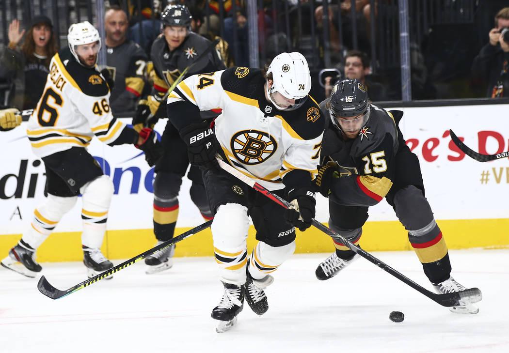 Boston Bruins' Jake DeBrusk (74) and Golden Knights' Jon Merrill (15) battle for the puck durin ...