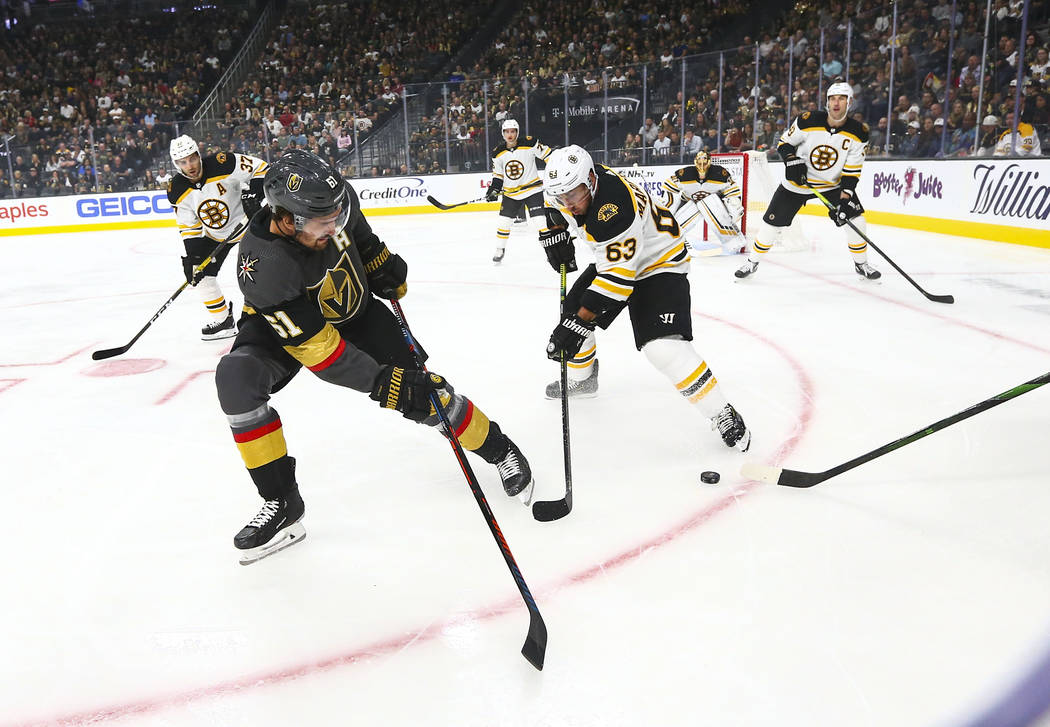 Golden Knights' Mark Stone (61) and Boston Bruins' Brad Marchand (63) battle for control of the ...