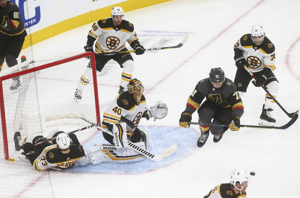 Golden Knights' William Karlsson (71) jumps out of the way of the puck as Boston Bruins goalten ...