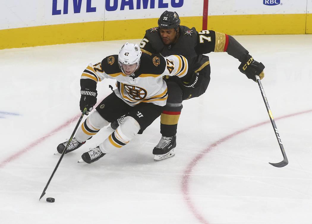 Boston Bruins' Torey Krug (47) skates with the puck under pressure from Golden Knights' Ryan Re ...