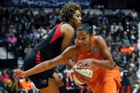 Connecticut Sun's Alyssa Thomas, front, drives past Washington Mystics' Tianna Hawkins during t ...