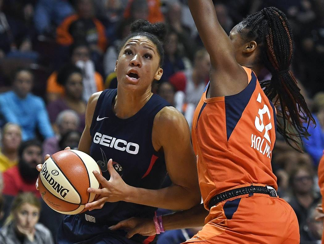 Washington Mystics' Aerial Powers, left, drives to the basket as Connecticut Sun's Bria Holmes ...