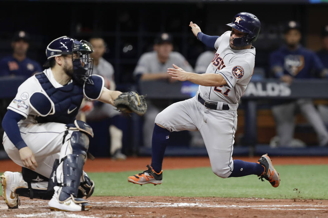 Houston Astros' Jose Altuve, right, heads for home, but is tagged out by Tampa Bay Rays catcher ...
