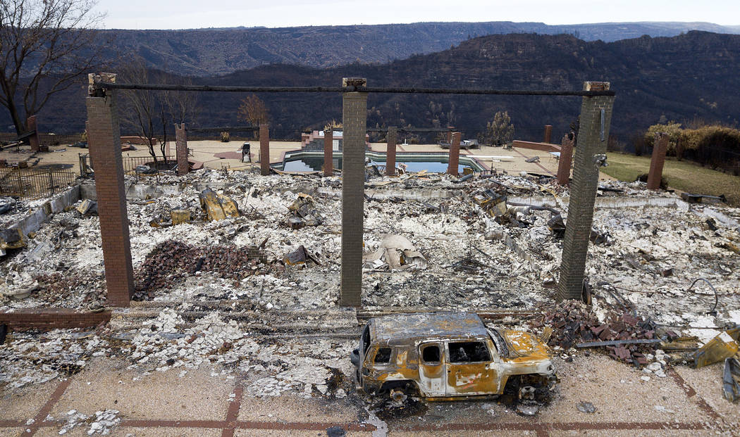 In this Dec. 3, 2018, file photo, a vehicle rests in front of a home leveled by the Camp Fire i ...